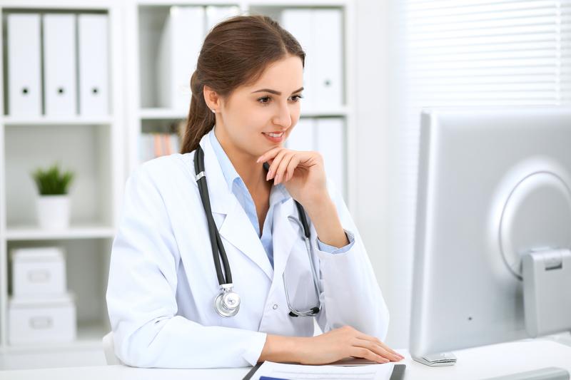 Ärztin sitzt an ihrem Schreibtisch und blickt interessiert auf Ihren Computerbildschirm